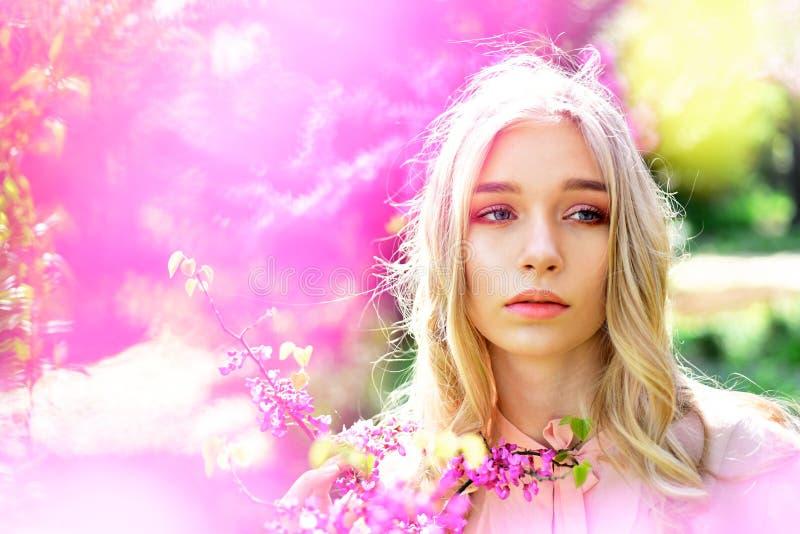 Muchacha hermosa con el maquillaje desnudo que presenta en jardín de la primavera Retrato de la mujer joven rubia con los ojos az imágenes de archivo libres de regalías