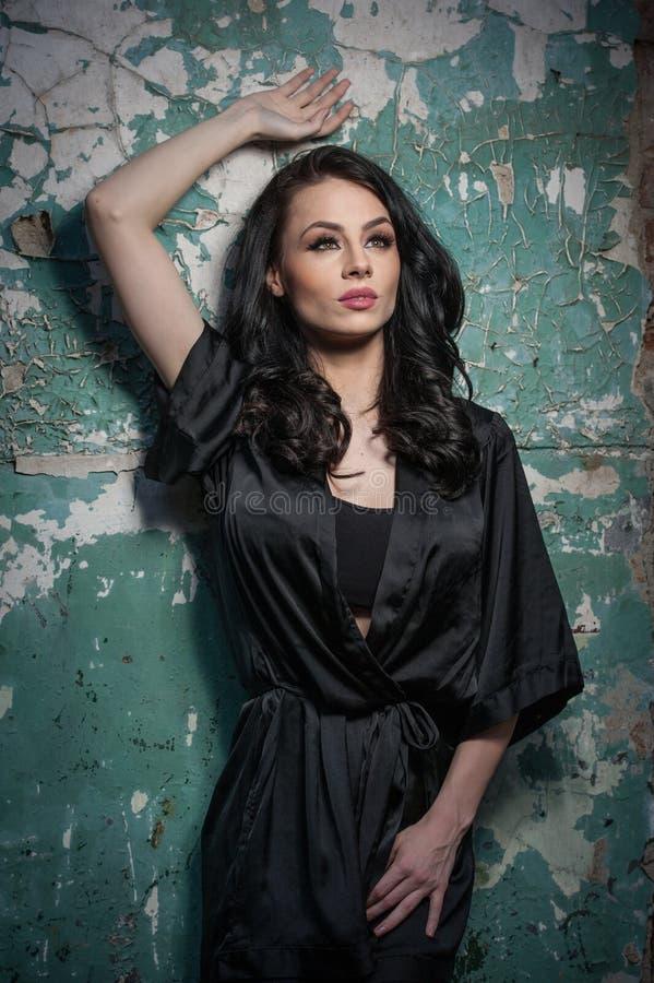 Muchacha hermosa con el maquillaje que presenta contra la pared vieja con la peladura de la pintura verde Brunette bonito en negr imagenes de archivo