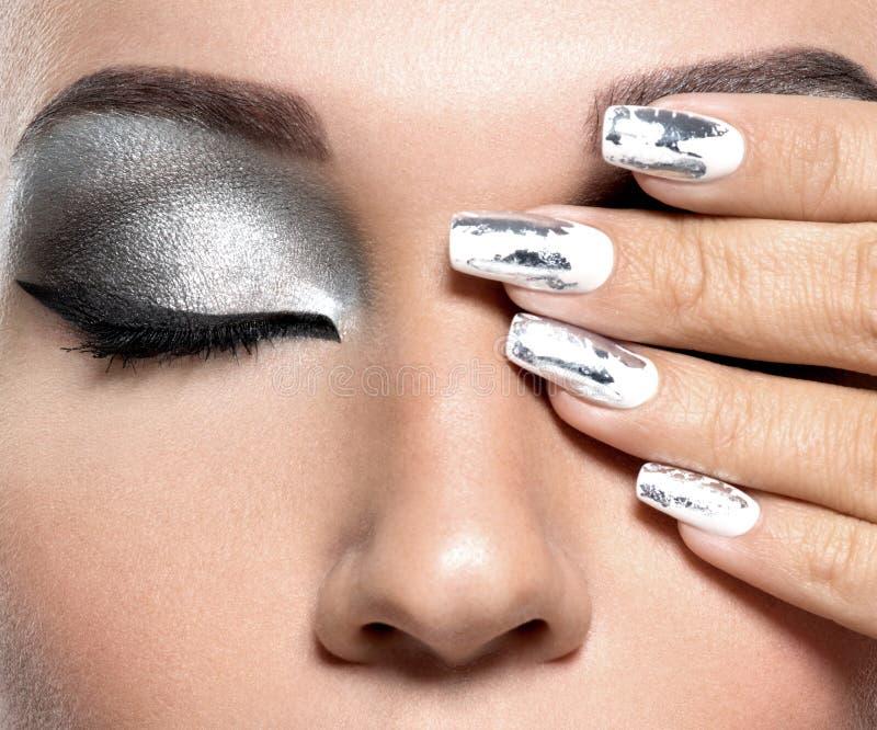 Muchacha hermosa con el maquillaje y los clavos de plata imagen de archivo