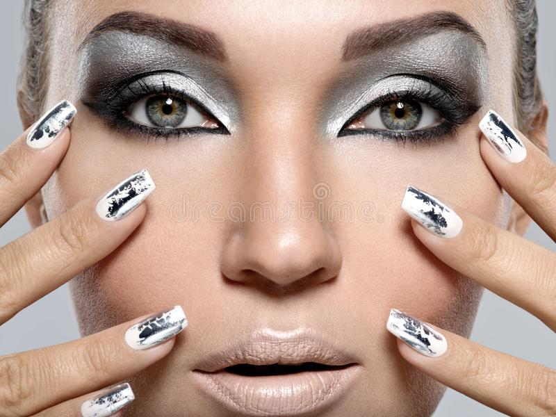 Muchacha hermosa con el maquillaje y los clavos de plata imagenes de archivo