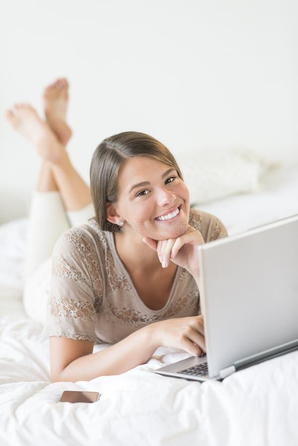 Muchacha hermosa con el ordenador portátil que miente en cama imagen de archivo libre de regalías