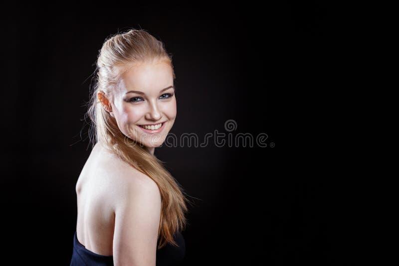 Muchacha hermosa con el peinado de la cola de caballo que sonríe en fondo negro imagenes de archivo