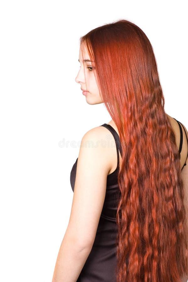 Muchacha hermosa con el pelo culry rojo largo imagen de archivo