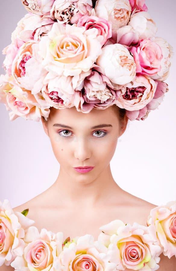 Muchacha hermosa con el pelo de las flores, el maquillaje y la piel de la seda, mirando la cámara foto de archivo