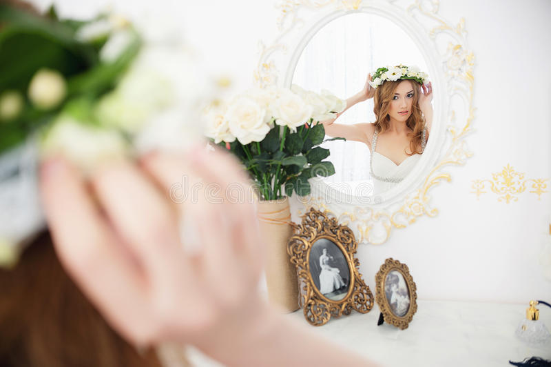 Muchacha hermosa con el pelo largo marrón que mira en un espejo que intenta en una guirnalda de flores Retrato de una mujer joven foto de archivo libre de regalías