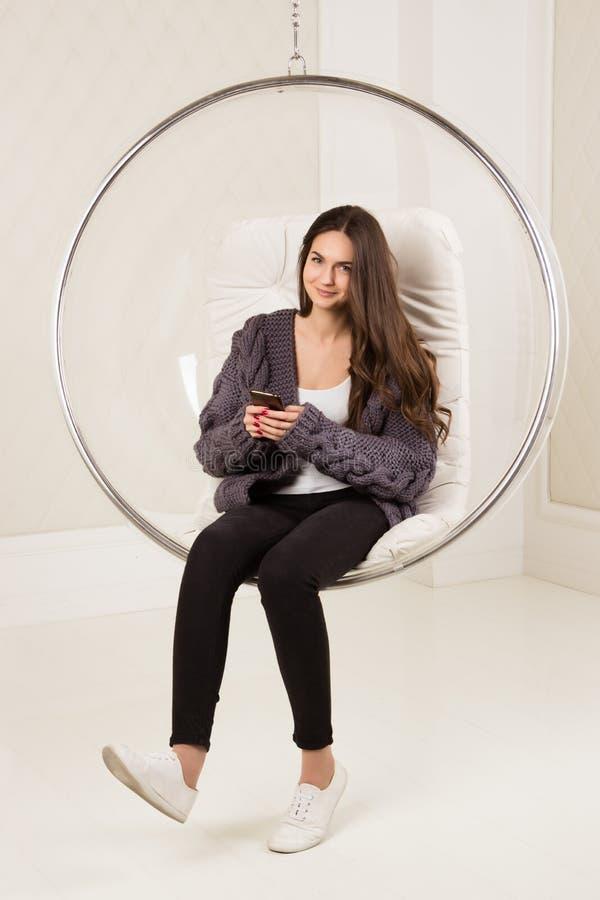 Muchacha hermosa con el pelo largo que toma el teléfono en manos en silla pendiente Imagen interior, entonada casera, proceso del imágenes de archivo libres de regalías