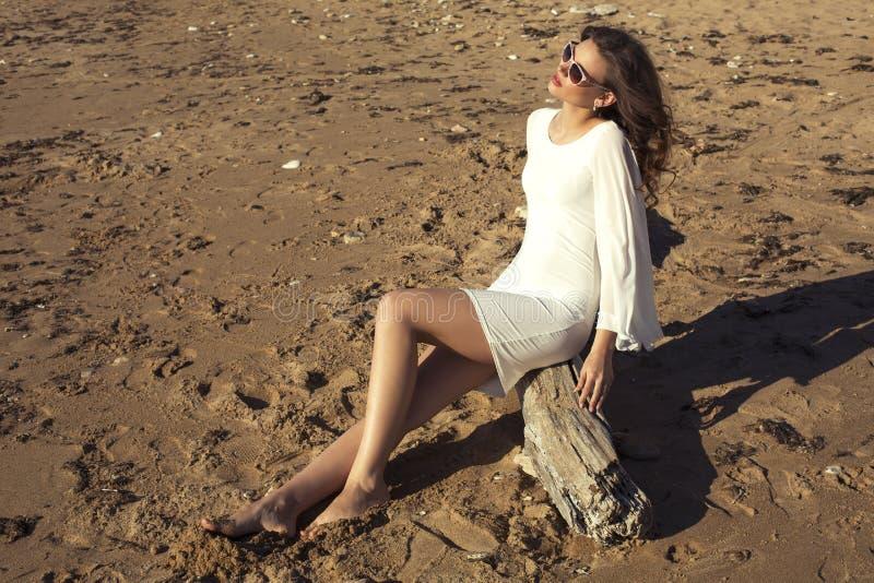 Muchacha hermosa con el pelo oscuro que presenta en la playa imagen de archivo libre de regalías