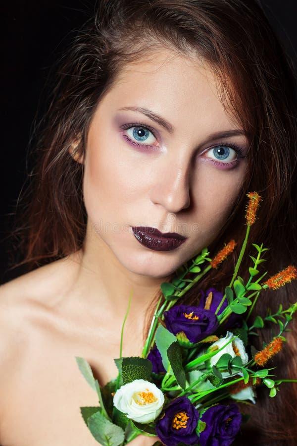 Muchacha hermosa con el pelo oscuro y maquillaje brillante con un ramo de flores púrpuras en el estudio en un fondo negro foto de archivo libre de regalías