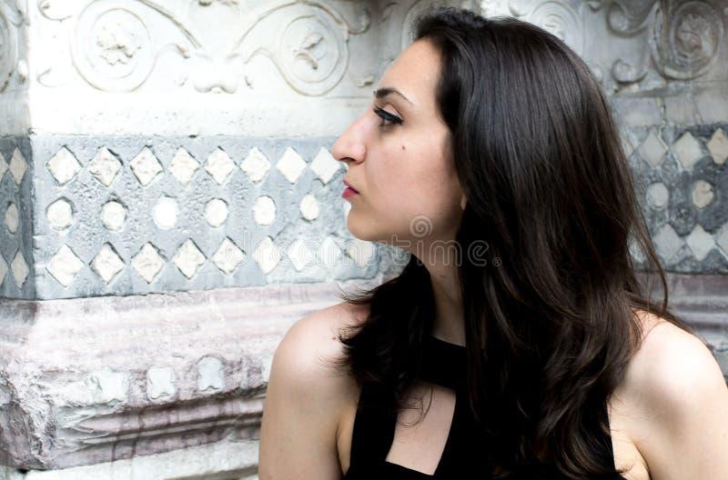 Muchacha hermosa con el pelo oscuro y un vestido negro imagenes de archivo