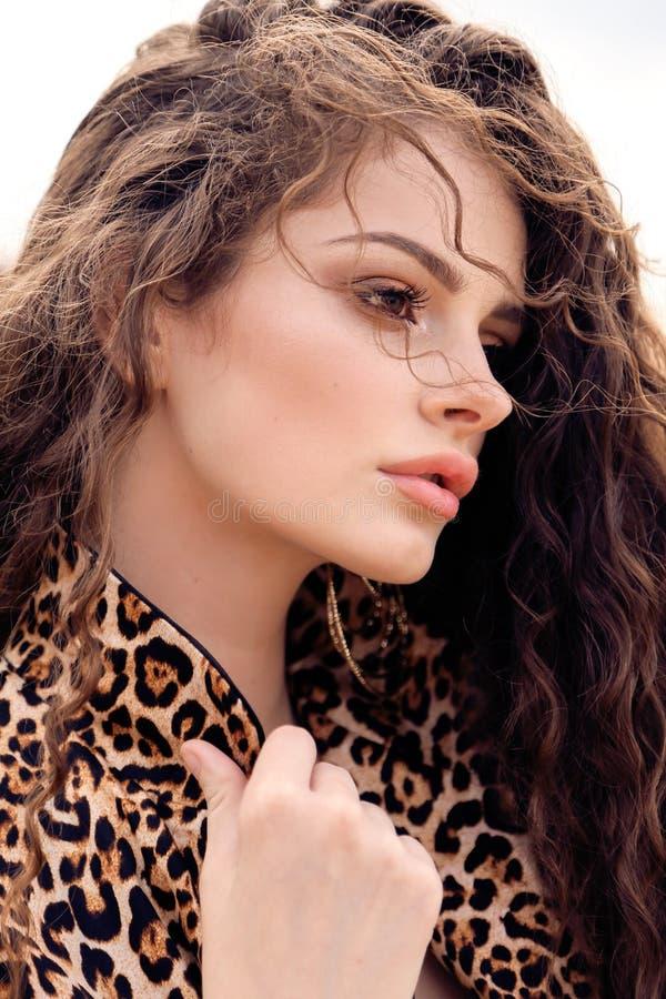 Muchacha hermosa con el pelo rizado oscuro en vestido elegante fotos de archivo