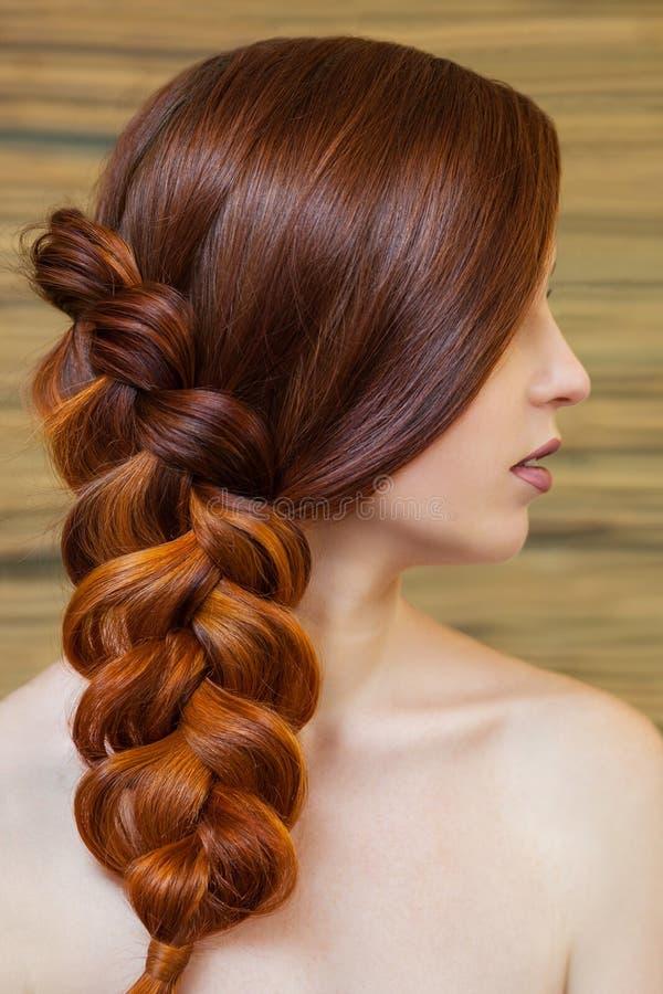 Muchacha hermosa con el pelo rojo largo, trenzado con una trenza francesa, en un salón de belleza fotografía de archivo