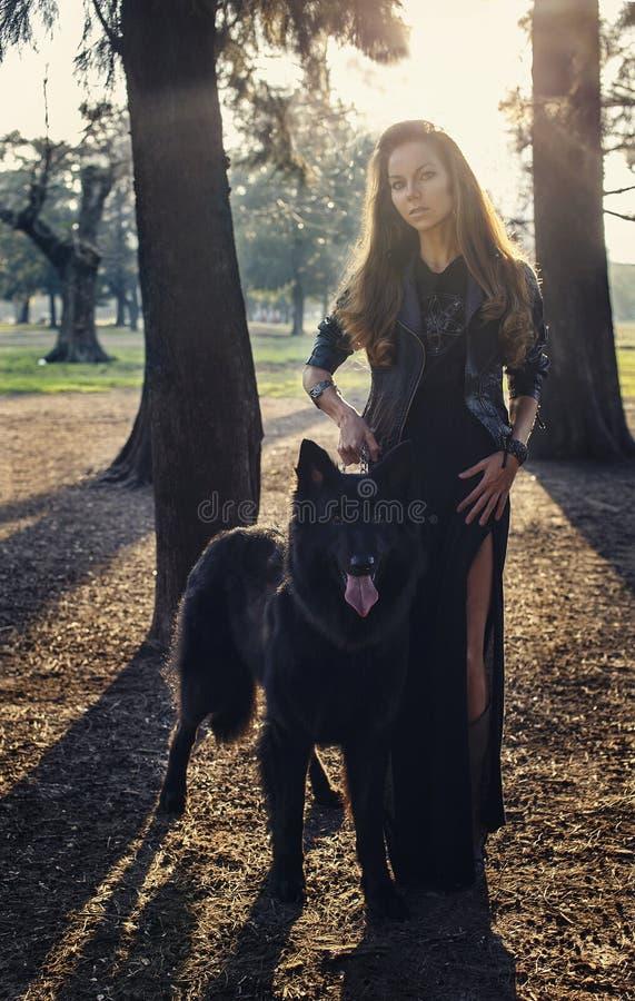 Muchacha hermosa con el perro negro grande fotos de archivo