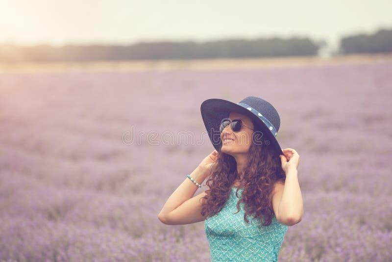 Muchacha hermosa con el sombrero, disfrutando del campo de la lavanda imagen de archivo libre de regalías