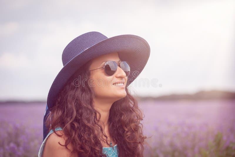 Muchacha hermosa con el sombrero, disfrutando del campo de la lavanda foto de archivo