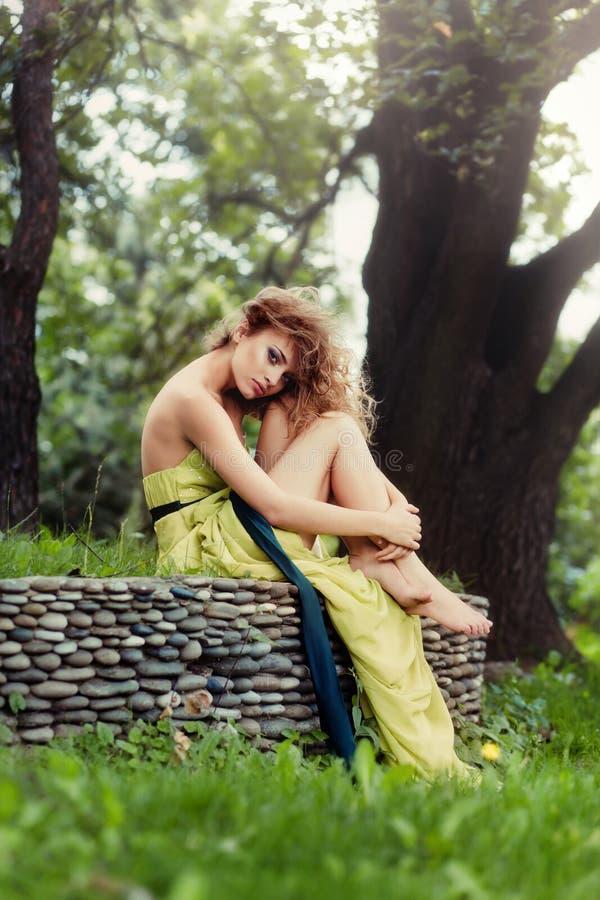 Muchacha hermosa con el vuelo del pelo en el viento que se sienta en la hierba fotografía de archivo