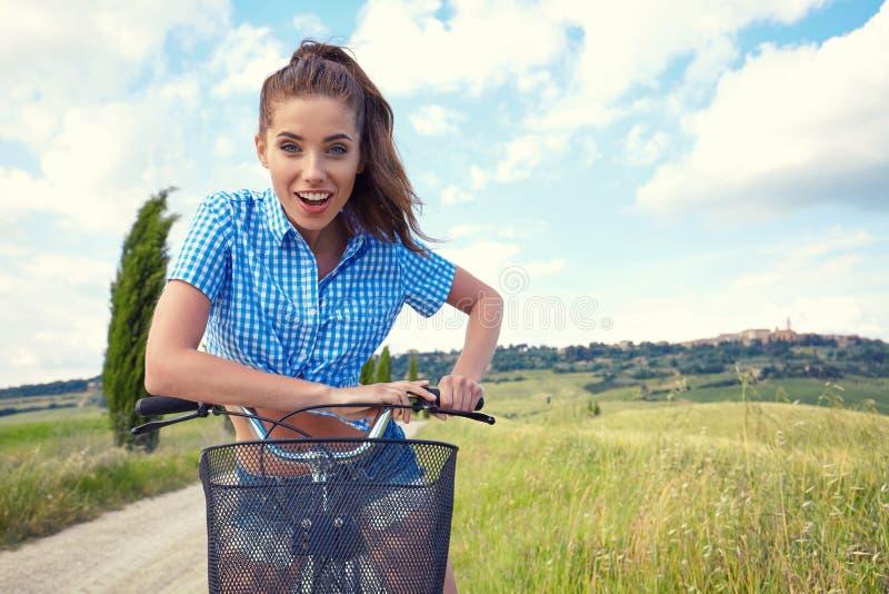 Muchacha hermosa con la bici al aire libre, tiempo del vintage de verano de Toscana foto de archivo