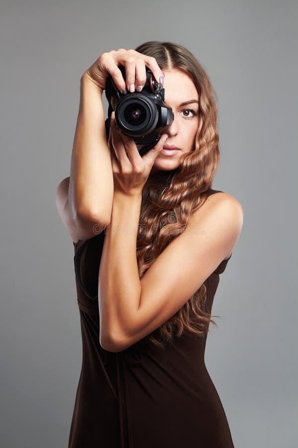 Muchacha hermosa con la cámara La mujer bonita es fotógrafo profesional fotografía de archivo
