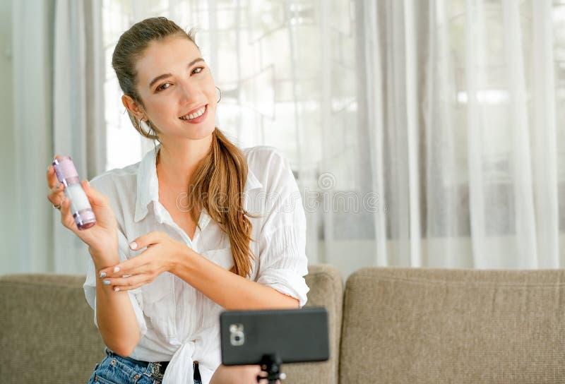 Muchacha hermosa con la demostración blanca de la camisa y el estudio vivo el producto cosmético en frente la cámara del teléfono fotografía de archivo