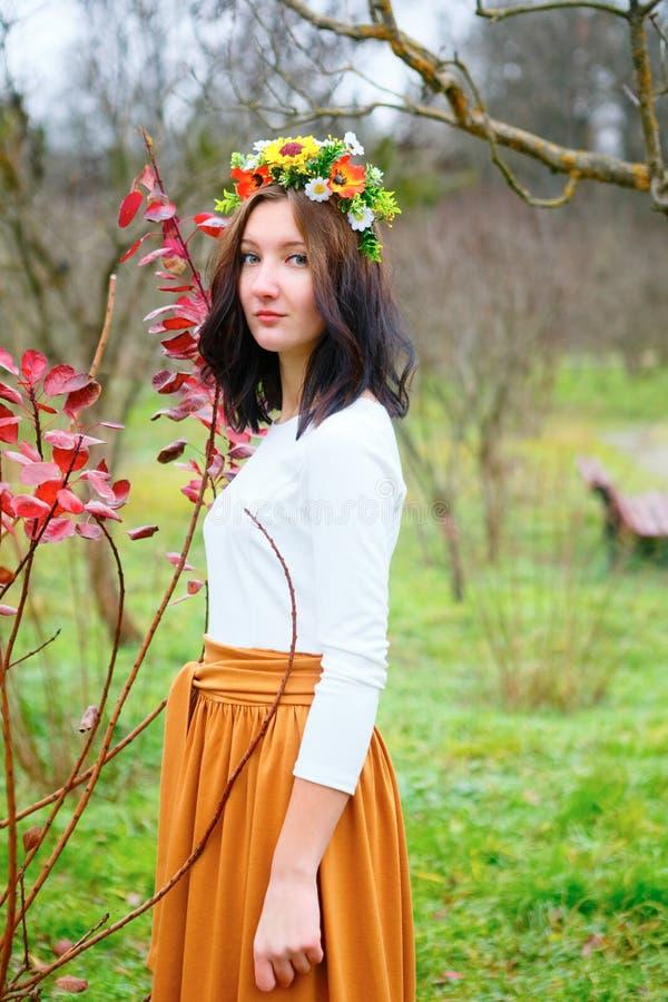 Muchacha hermosa con la guirnalda de la flor en el parque colorido del otoño foto de archivo