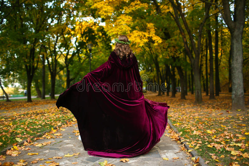 Muchacha hermosa con la linterna en la madera asustadiza del otoño Imagen de la fantasía y de Halloween Mujer vestida en el parqu imagenes de archivo
