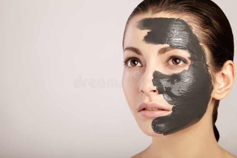 Muchacha hermosa con la máscara de la arcilla en su cara imagen de archivo