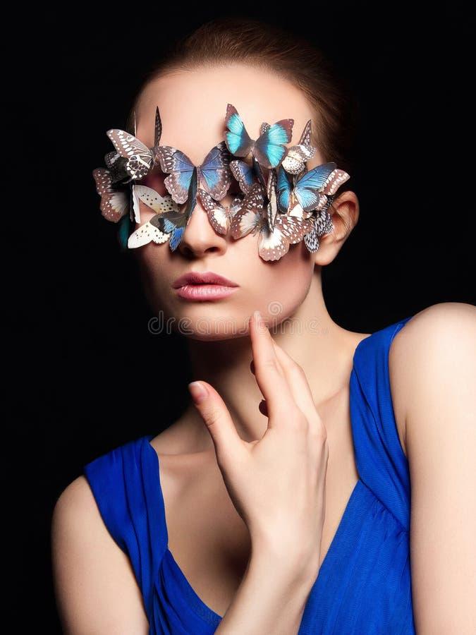 Muchacha hermosa con la máscara inusual de las mariposas foto de archivo libre de regalías