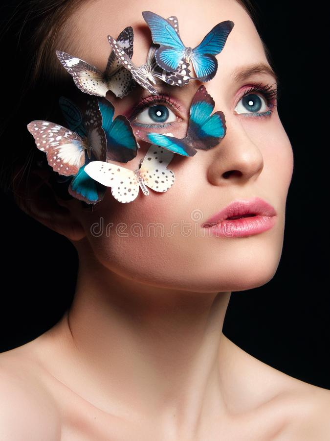 Muchacha hermosa con la máscara inusual de las mariposas fotos de archivo