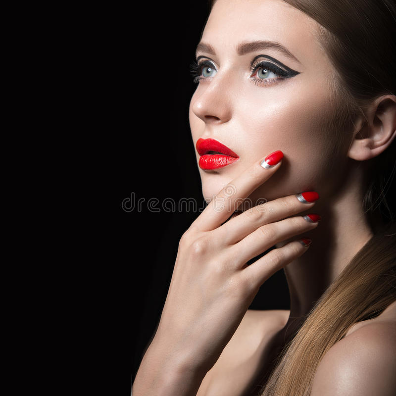 Muchacha hermosa con las flechas negras inusuales en ojos y labios y clavos del rojo Cara de la belleza imágenes de archivo libres de regalías