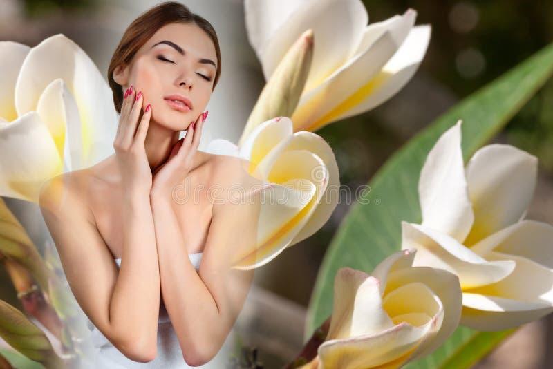 Muchacha hermosa con las flores blancas del frangipani foto de archivo