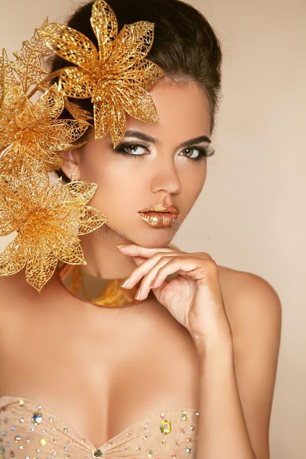 Muchacha hermosa con las flores de oro. Belleza Woman Face modelo. Por fotografía de archivo
