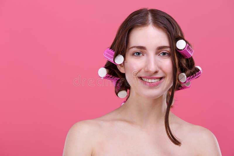 Muchacha hermosa, con los bigudíes de pelo en el pelo y envueltos en toalla de baño, sonrisa linda Fondo rosado foto de archivo libre de regalías