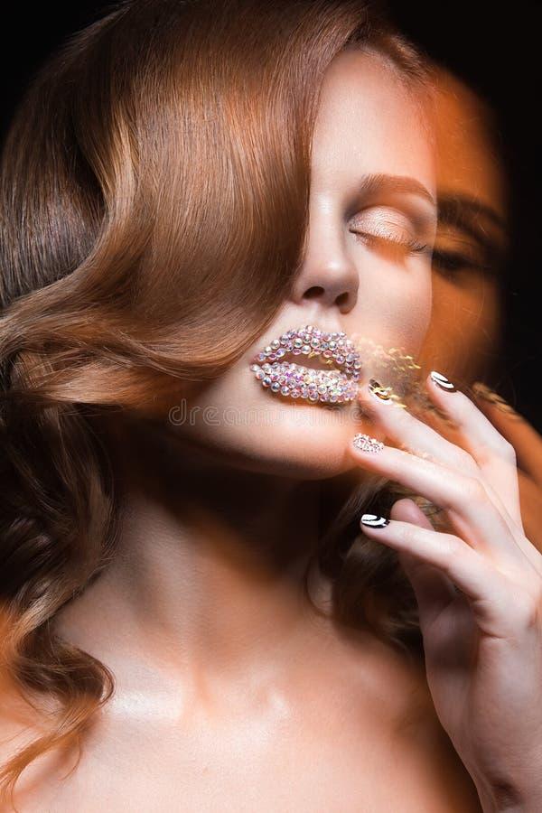 Muchacha hermosa con los clavos y los labios brillantes de cristales, de pestañas largas y de rizos Cara de la belleza foto de archivo libre de regalías
