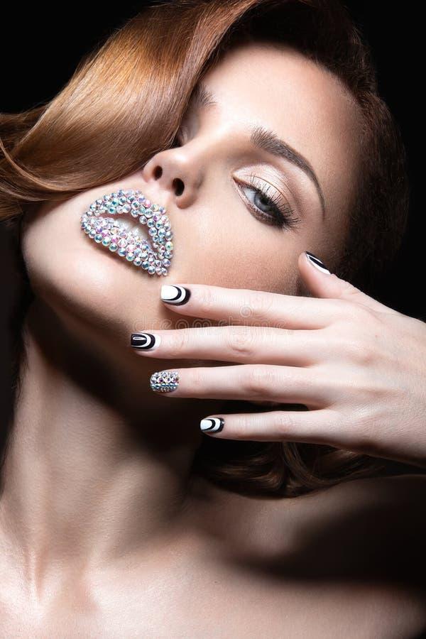 Muchacha hermosa con los clavos y los labios brillantes de cristales, de pestañas largas y de rizos Cara de la belleza imagen de archivo
