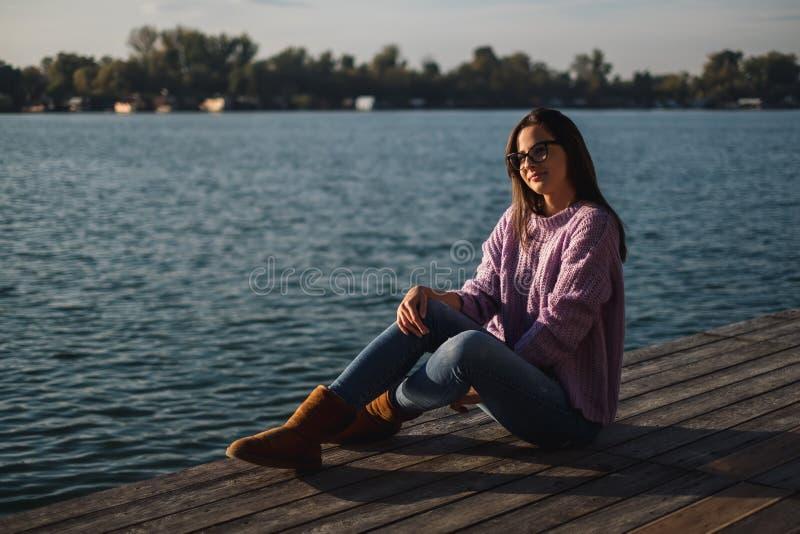 Muchacha hermosa con los vidrios que se sientan por el río en puesta del sol fotos de archivo