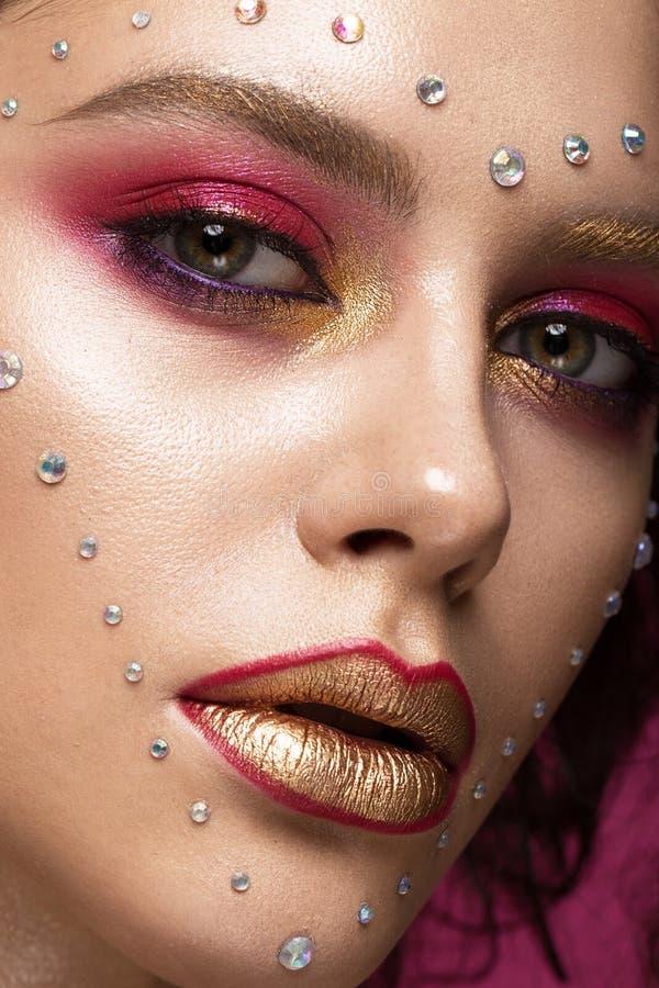Muchacha hermosa con maquillaje brillante de la moda, y corazón de cristales en la cara Día del `s de la tarjeta del día de San V imágenes de archivo libres de regalías