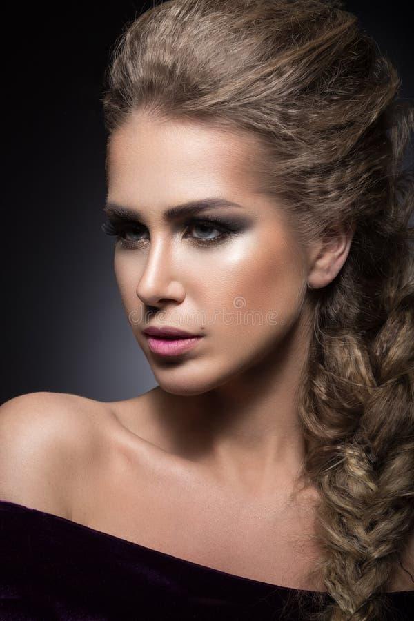 Muchacha hermosa con maquillaje brillante, piel perfecta y el peinado como trenza foto de archivo