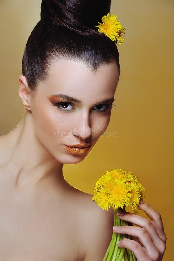 Muchacha hermosa con maquillaje brillante y flores amarillas en manos foto de archivo