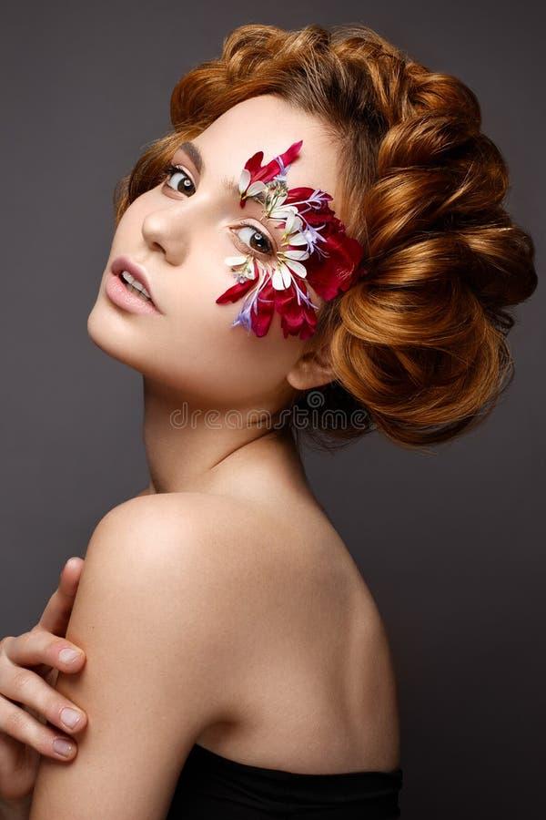 Muchacha hermosa con maquillaje creativo con appliques florales El modelo en el estilo de romántico con los pétalos de la flor al imagen de archivo