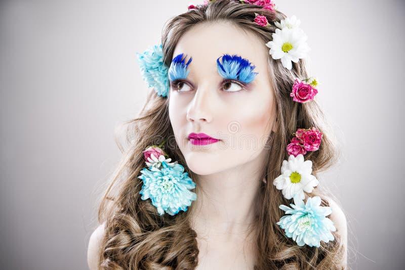 Muchacha hermosa con maquillaje creativo y peinado con las flores fotos de archivo