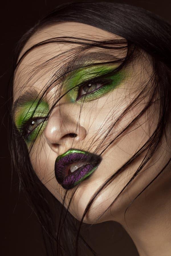 Muchacha hermosa con maquillaje del verde de la primavera y labios del vampiro Cara de la belleza imagen de archivo libre de regalías