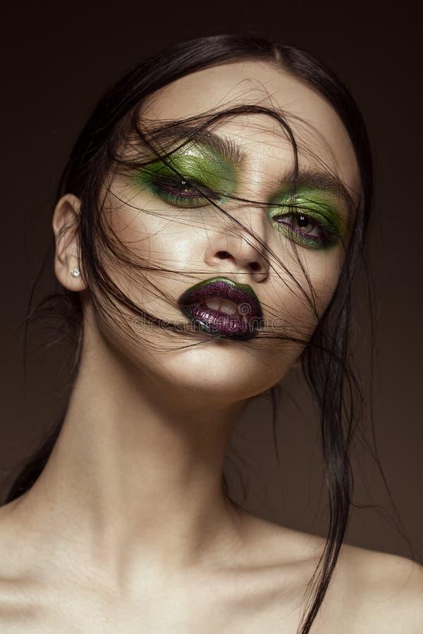 Muchacha hermosa con maquillaje del verde de la primavera y labios del vampiro Cara de la belleza imagen de archivo