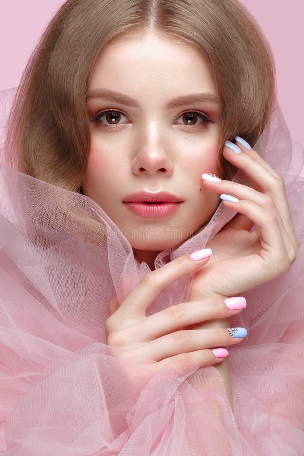 Muchacha hermosa con maquillaje ligero y manicura apacible en ropa rosada Cara de la belleza Clavos del diseño imagenes de archivo