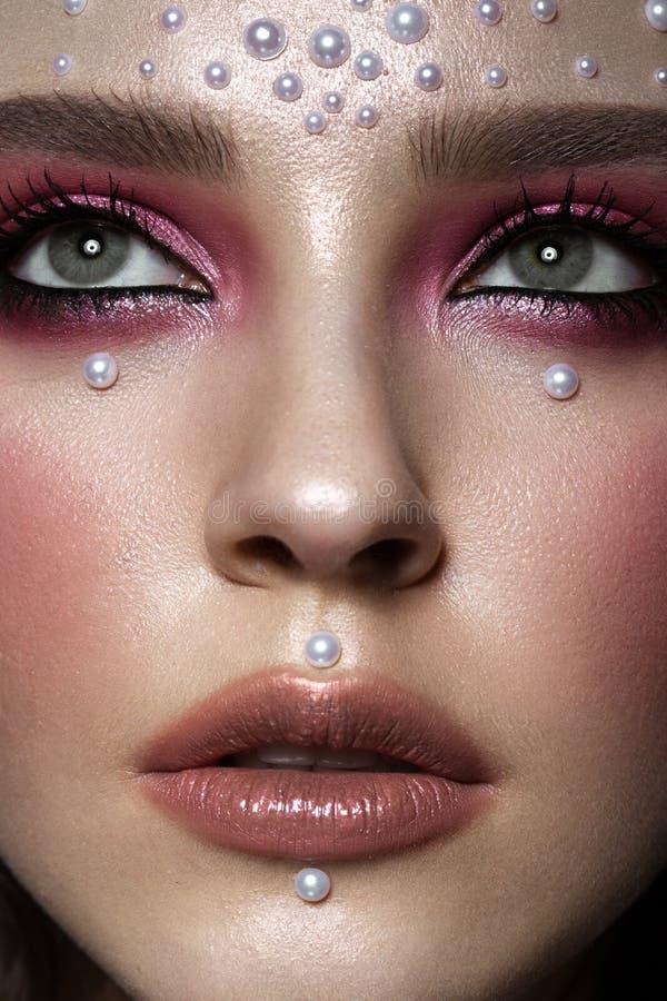 Muchacha hermosa con maquillaje perfecto del arte y gotas de la perla Cara de la belleza imagen de archivo