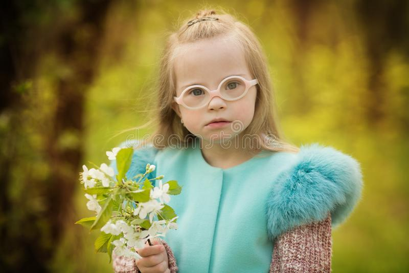 Muchacha hermosa con Síndrome de Down que sostiene las flores de la primavera imagen de archivo