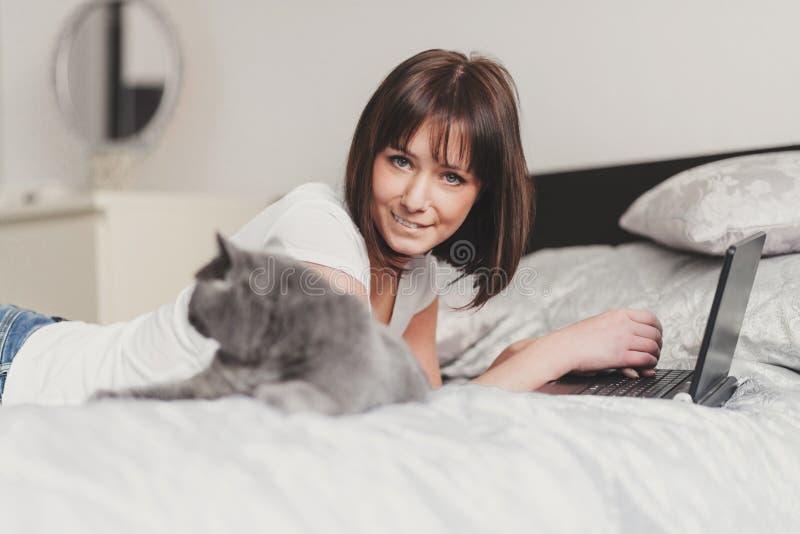 Muchacha hermosa con su gato que trabaja en el ordenador portátil fotografía de archivo libre de regalías