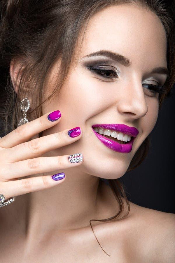 Muchacha hermosa con un maquillaje brillante de la tarde y manicura púrpura con los diamantes artificiales Diseño del clavo Cara  fotos de archivo