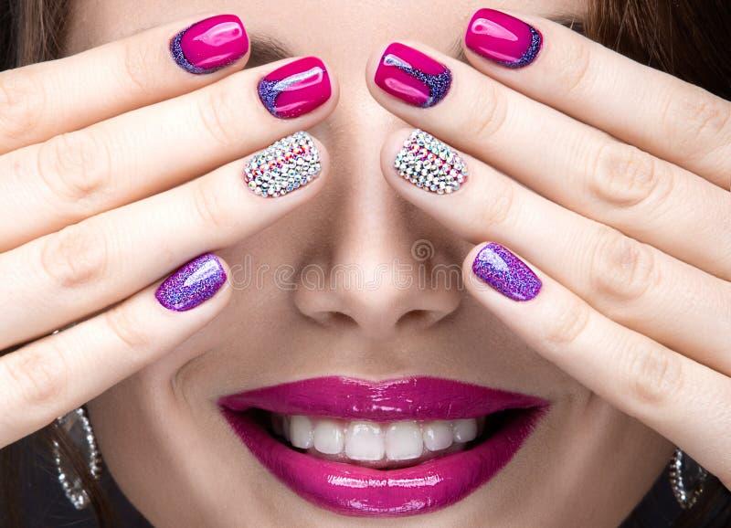 Muchacha hermosa con un maquillaje brillante de la tarde y manicura rosada con los diamantes artificiales Diseño del clavo Cara d fotos de archivo libres de regalías