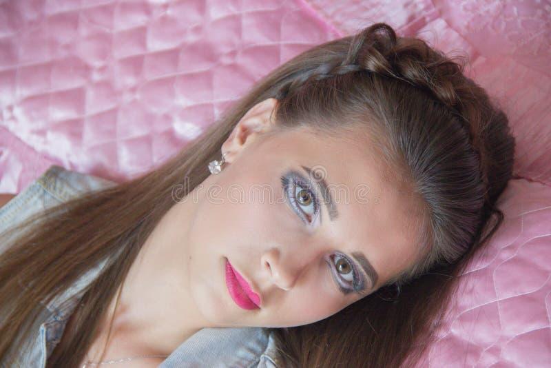 Muchacha hermosa con un maquillaje de una barbie y de un pelo largo en un dormitorio rosado imagen de archivo libre de regalías