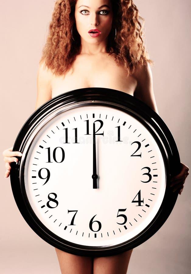 Muchacha hermosa con un reloj de pared fotos de archivo