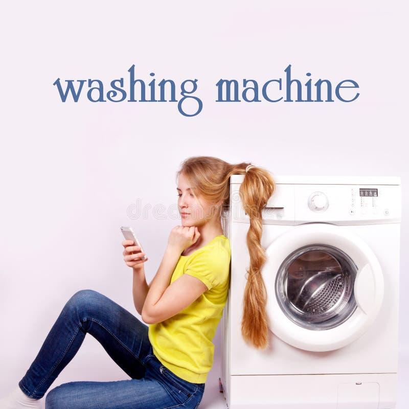Muchacha hermosa con un teléfono móvil y una lavadora aislados foto de archivo
